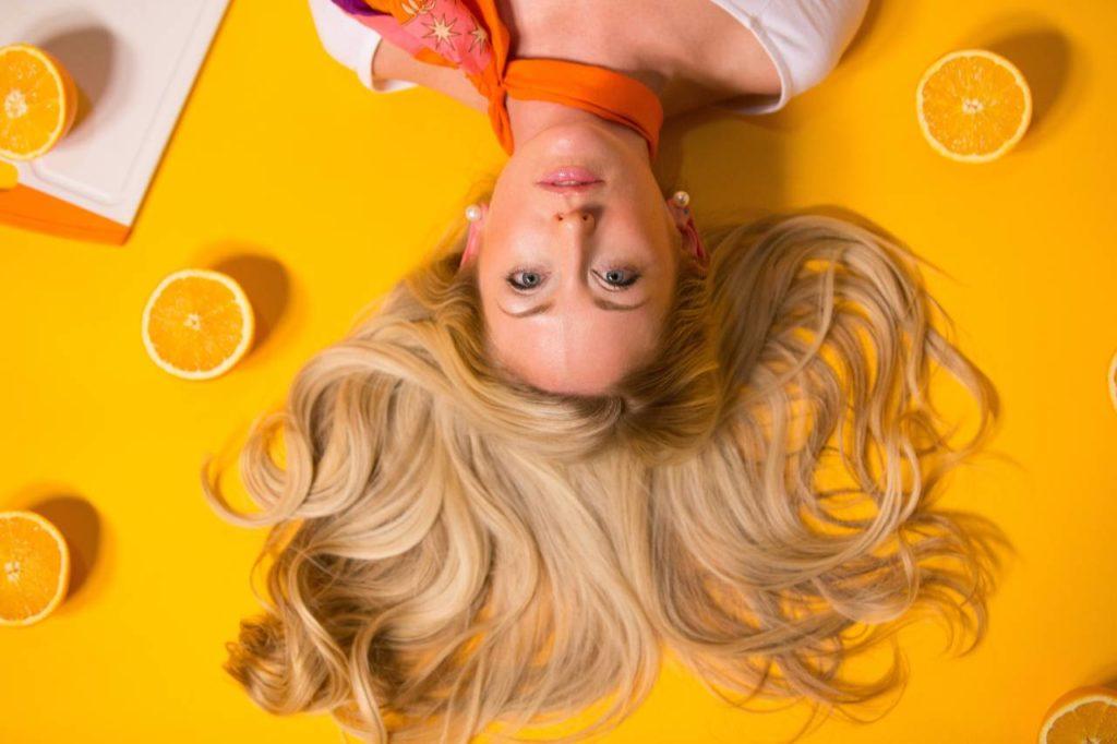 woman with blonde hair oranges around